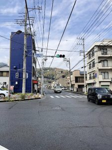 Street intersection with blue building on the left and the hill raising in the background.